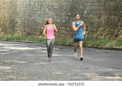 Young man and woman running in city