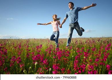 Young man and woman running on countryside meadow with pink flowers