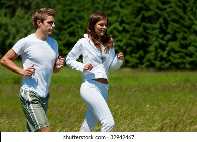 Young man and woman running outdoors on a sunny day, shallow DOF