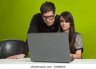 Young man and woman sitting in the office and working on the laptop