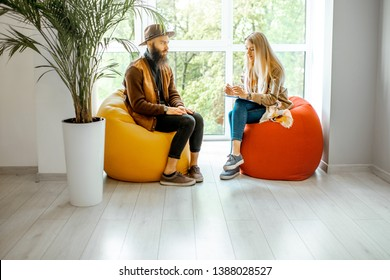 Young Man And Woman Sitting On The Comfortable Chairs During The  Psychological Counseling, Solving Some