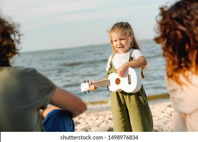 Young man and woman sitting on a beach while their cute little daughter playing on ukulele for them