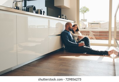 Young man and woman sitting on floor in kitchen and talking. Loving young couple spending time together at home.