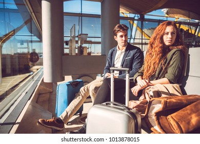 Young man and woman sitting with suitcases in waiting room in terminal of airport.