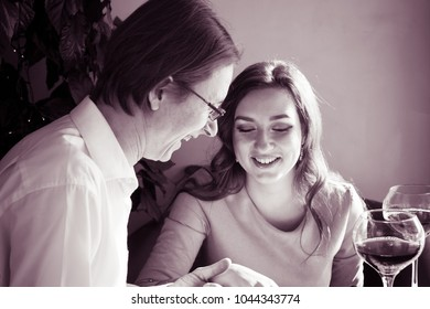 Young man and woman are sitting at the table and laughing. On the table are glasses of wine. a meeting or a date in a restaurant or cafe.