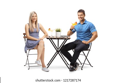 Young man and woman sitting at a table with cocktails isolated on white background