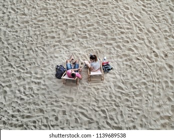 Young man and woman sitting, talking and drinking on city beach. Top down view.  Bratislava, Slovakia, Europe, July 2018.