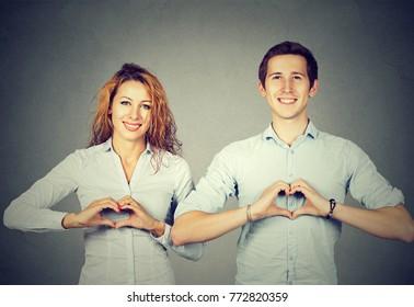 Young man and woman smiling at camera gesturing hearts on gray backdrop.