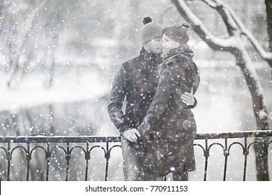 young man and woman in the snow in a city park couple winter