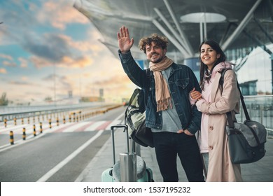 Young man and woman stand outside airport and wait for taxi cab. Guy wave with hand. After vacation or travel. Georgian woman hold his hand and smile. Sunset outside. Evening
