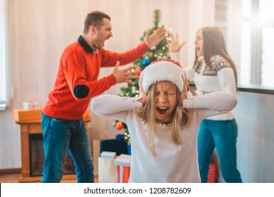 Young man and woman standing in front of each other and screaming. They argue. Girl stand in front of camera and close her ears. She is screaming too. Girl is suffering.