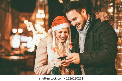 Young man and woman standing in the street in Christmas eve and having fun while looking at smartphone.