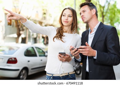 Young man and woman strolling through city streets and pointing each other something