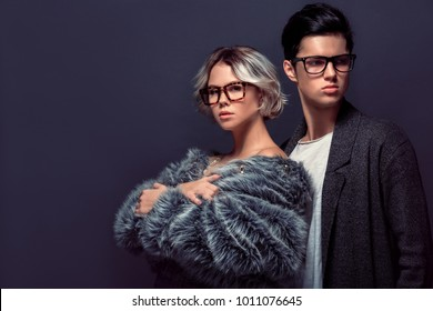 Young man and woman studio shoot isolated on grey wall fashion professional