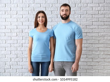 Young man and woman in stylish t-shirts near white brick wall. Mockup for design