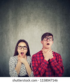 Young man and woman suffocating themselves looking irritated with being in relationship and looking up