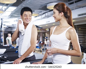 young man and woman talking during a break in gym.