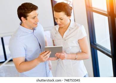 Young man and woman with touchpad standing in office