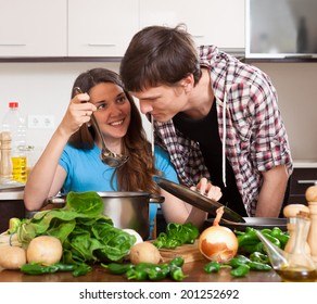 young man and the woman try the cooked food in kitchen
