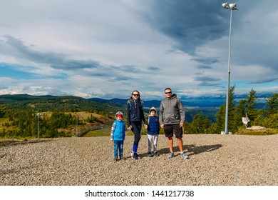 young man and woman and two children stand on the mountain against the blue cloudy sky in autumn