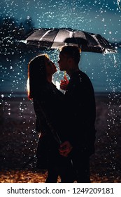 young man and woman under an umbrella and rain.