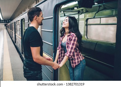 Young man and woman use underground. Couple in subway. Young brunette stand in underground carriage and smile. She hold man's hands. Guy stand on platform. Love stiry. Cheerful.
