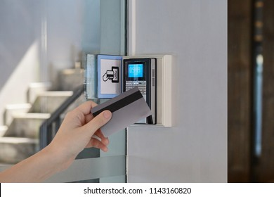 Young man or woman used key card for access digital door systems. People holding key card for unlocking door. Selective focus. Close up