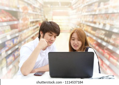 Young man and woman using laptop for shopping online. blur supermaket as background .The concept of online shopping, online payment, financial and internet of things.