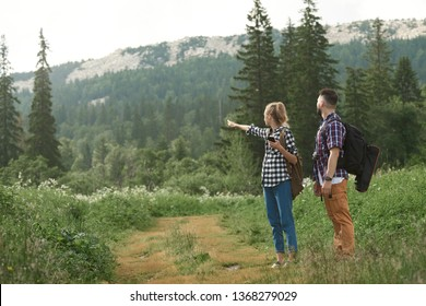 Young man and woman using smart phone to lacate and navigate while backpacking in the forest at summer