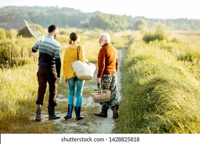 Young man and woman walking on the picnic with senior grandfather dressed in sweaters, spending a good time together on the nature