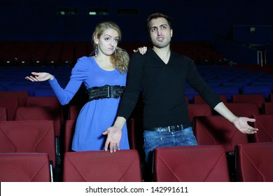Young man and woman watch movie and are confused in cinema theater.