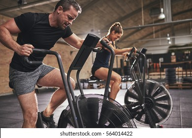 Young man and woman wearing training hardly on cycling machines in light spacious gym.