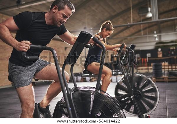 Jeune homme et femme portant un entraînement à peine sur des machines à vélo dans un gymnase spacieux et lumineux.