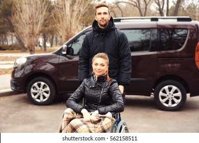 Young man with woman in a wheelchair in front of his car