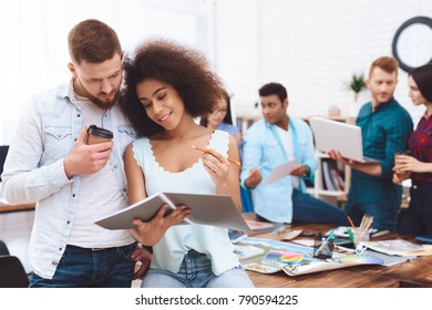 Young man and woman working together in the office. A young girl and a white man are examining documents.