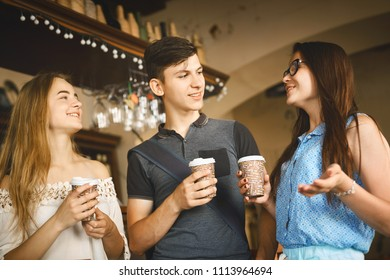 Young man and women with paper cups standing at bar counter in cafe, laughing and talking. Group of friends enjoying in cafe together. Young people meeting in a cafe.
