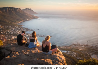Young man and women sitting on the rock on top of Lion's head mountain look at the Atlantic Ocean and Cape town city view in South Africa