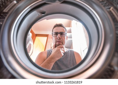 Young man wondering how the washing machine works.