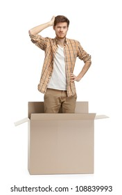 Young man wonders why he is inside the box, isolated, white background