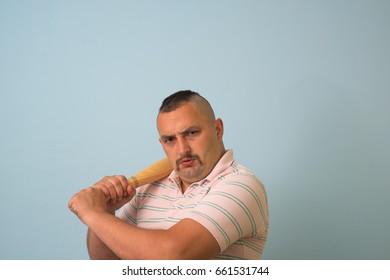 Young man with wooden baseball bat, on grey background.