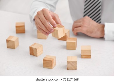 Young man with wooden cubes at table