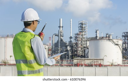 young man in work wear clothing and Safety helmet , reviewing the plans on his notebook.gas refinery , oil industry