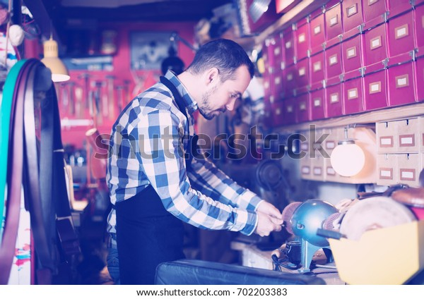Young man worker working on belt buckle in leather workshop