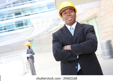 A young man working as architect on a construction site with coworker in background