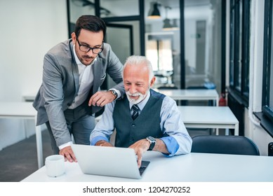 Young man working with boss or older employee in the office.