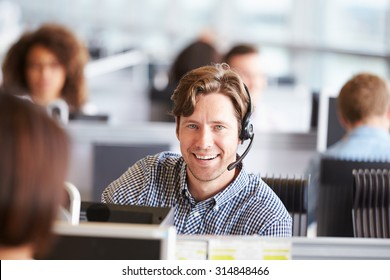 Young man working in call centre, looking to camera