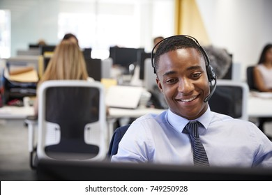 Young man working at computer with headset in busy office