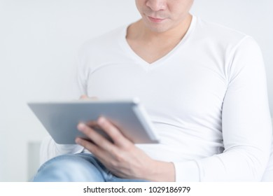 Young man working with digital tablet at home. selective focus at his mouth.