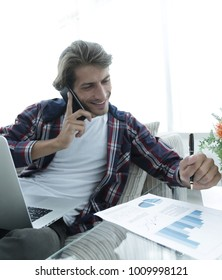 young man working with financial documents sitting on sofa in living room
