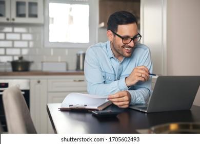 Junge Menschen, die von zu Hause aus Papierarbeit machen, während sie Laptop benutzen und Stift in der Hand halten.